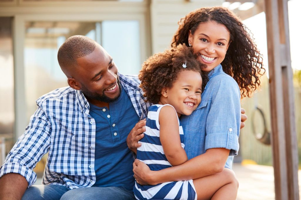 Black family embracing outdoors smiling to camera outside